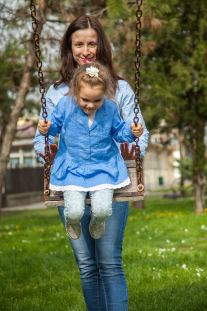 Mother pushing daughter on swing stock photo