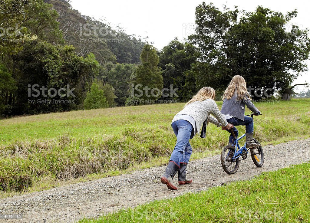 Mother pushing daughter up hill on her bicycle royalty-free stock photo