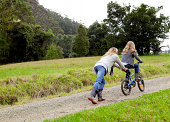 istock Mother pushing daughter up hill on her bicycle 84751432