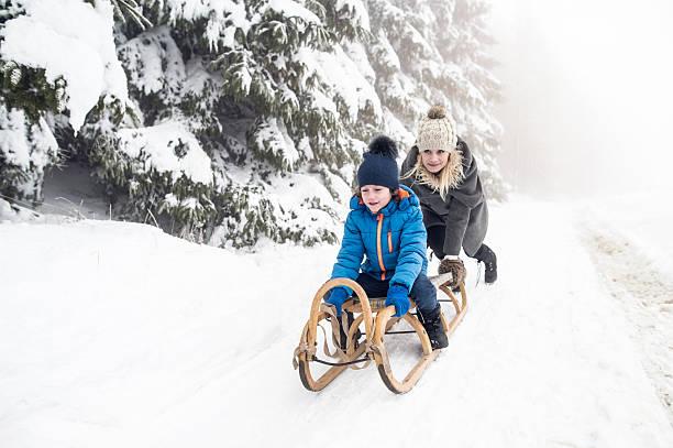 mother pushing son on sledge. foggy white winter nature. - wintermantel damen wolle stock-fotos und bilder