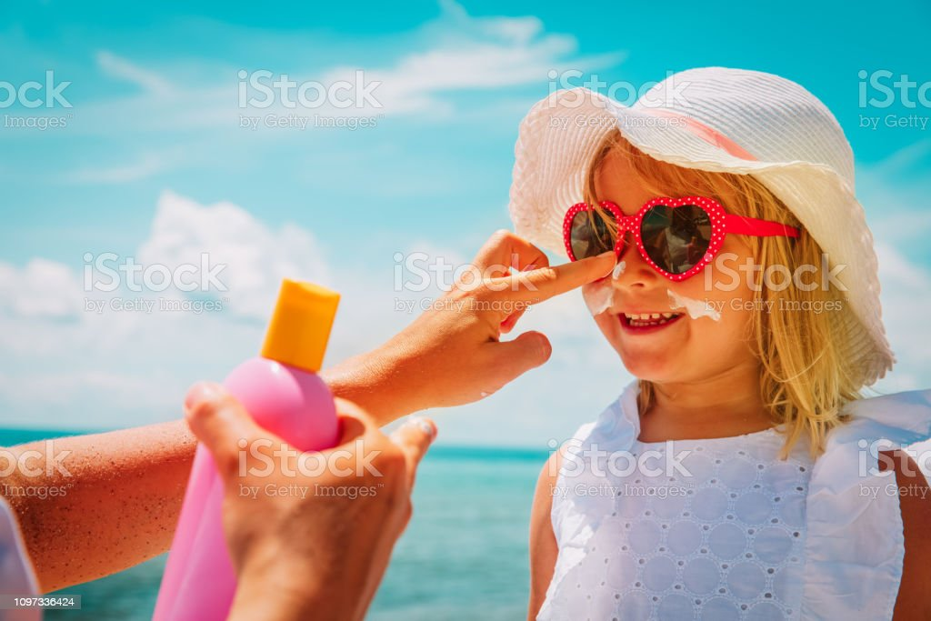 mother put sunblock cream on little daughter face at beach stock photo