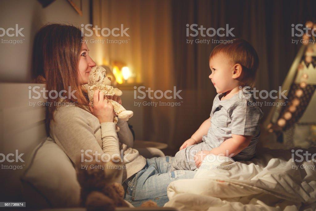 mãe coloca o filho bebê para dormir de noite na cama - foto de acervo