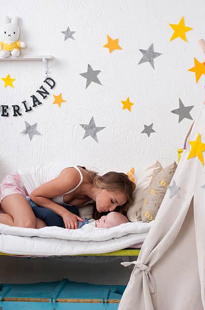 mutter bringt das baby schlafen - tipi bett stock-fotos und bilder