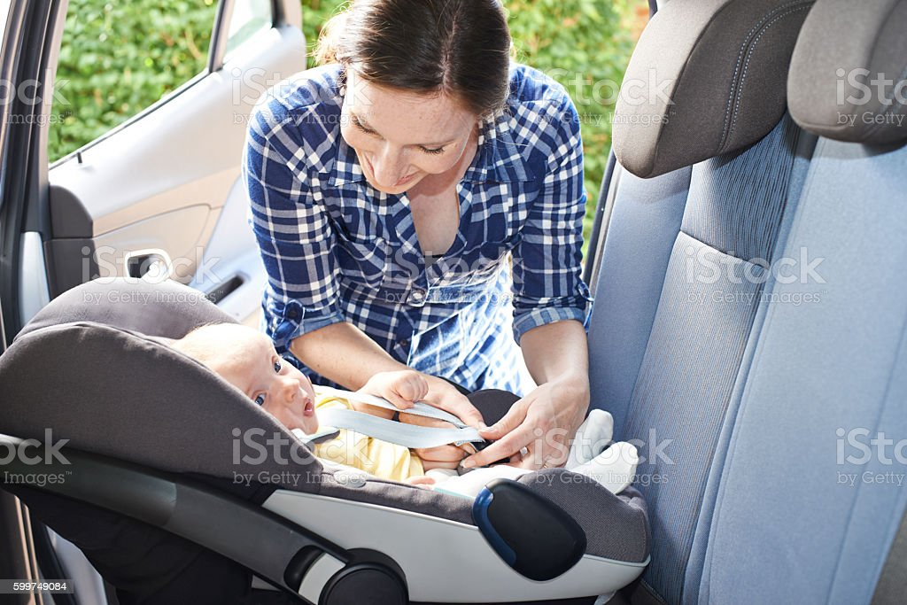 Mother Putting Baby Into Car Seat For Journey stock photo