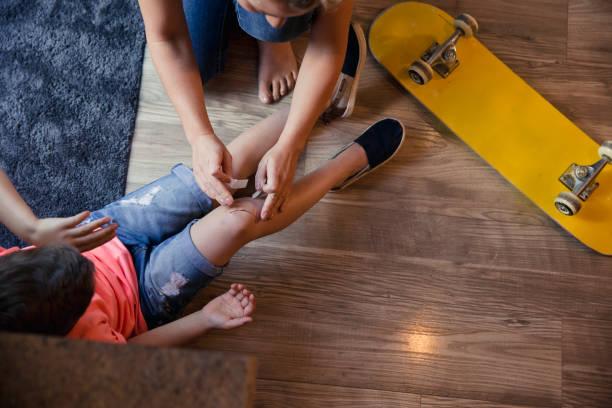 Mère de mettre des pansement sur les genoux des Childs. - Photo