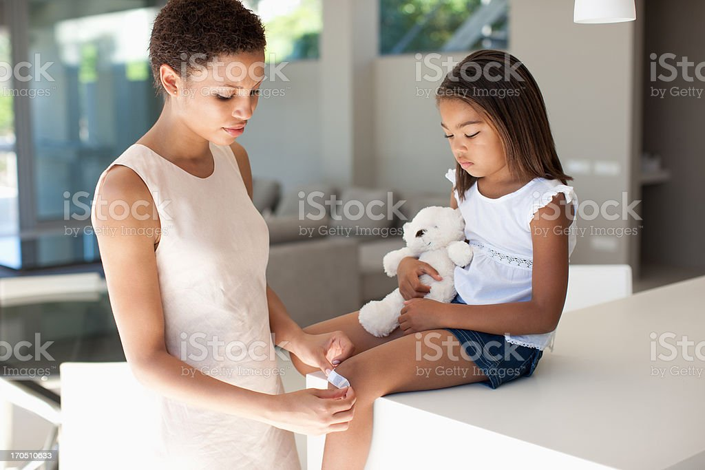 Mother putting bandage on daughter knee royalty-free stock photo