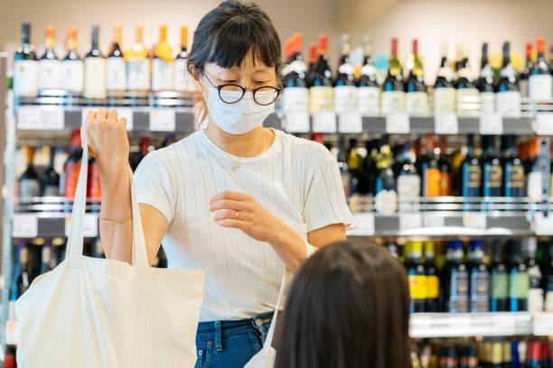 母親は娘と一緒に保護フェイスマスクを着用しながら、スーパーマーケットで再利用可能なショッピングバッグに食料品を入れて - sustainability ストックフォトと画像