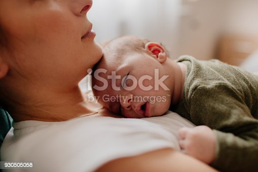 Photo of a young mother holding her newborn baby, while putting him to sleep
