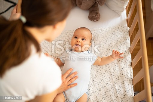 Mother leaning over side of crib and talking to her baby boy. Child looking at mum and smiling