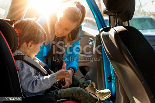 Young mother putting her little boy in the car seat, fastening seat belts.
