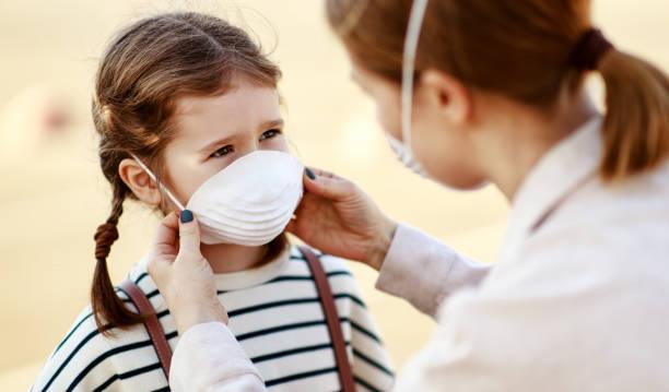 mère mettant sur le masque médical sur la fille - masque enfant photos et images de collection