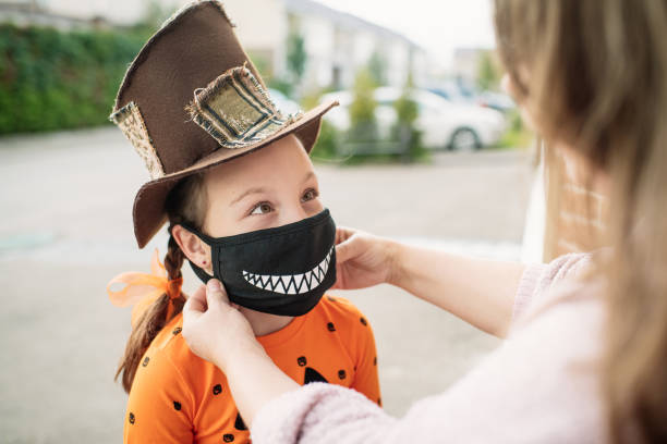 Mother putting protective face mask on her child during COVID-19 pandemic on Halloween Little girl getting ready for Halloween halloween covid stock pictures, royalty-free photos & images