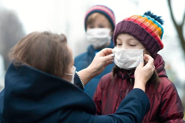 Mutter setzt schützende Gesichtsmaske auf ihre Kinder – Foto