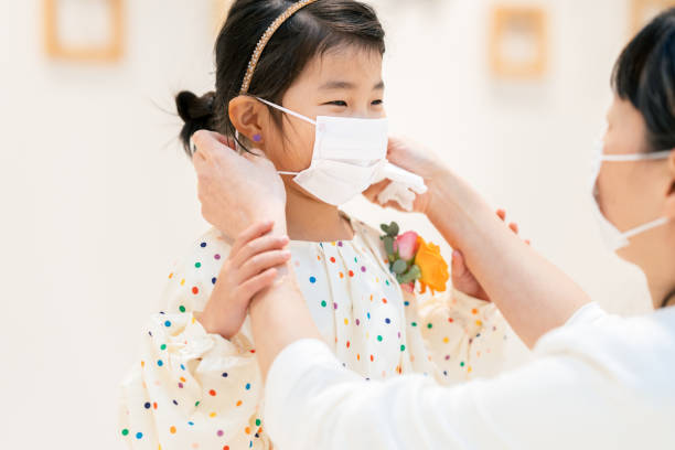 Mother putting protective mask on her daughter`s face stock photo