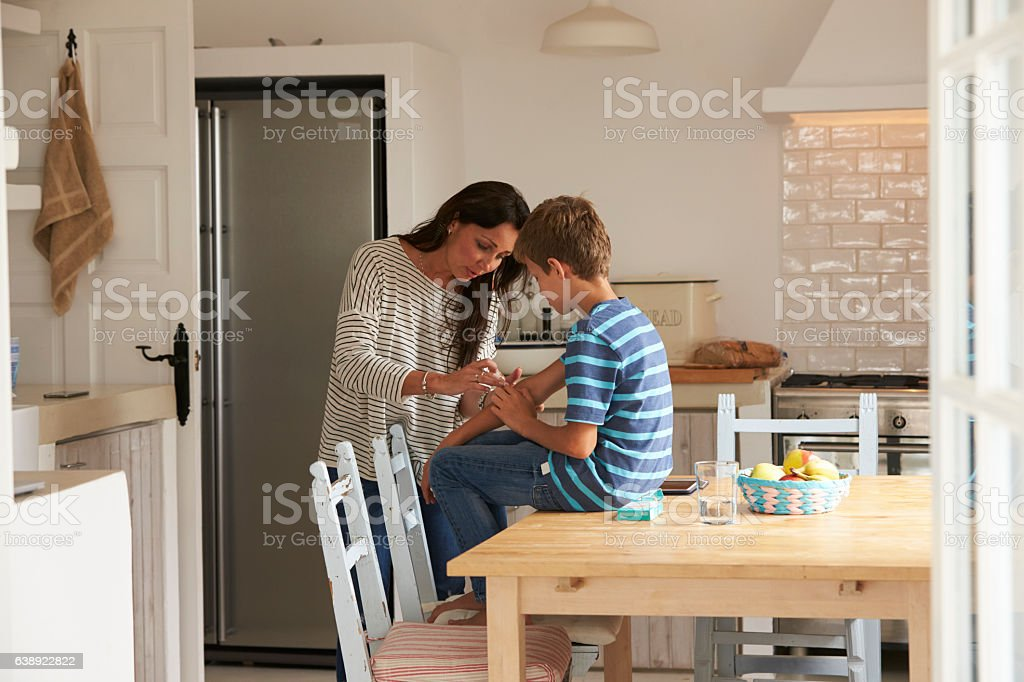 Mother Putting Sticking Plaster On Son's Arm stock photo