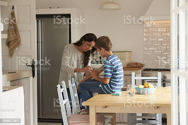 Mutter Putting Sticking Gips Auf Sohn Arm Stockfoto und mehr Bilder von Pflaster