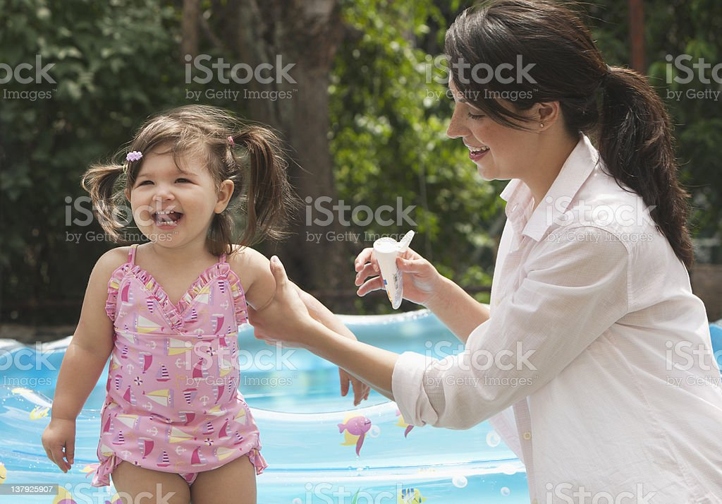 Mother putting sunscreen on baby daughter royalty-free stock photo