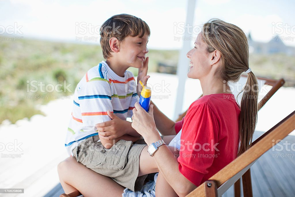 Mother putting sunscreen on boy stock photo