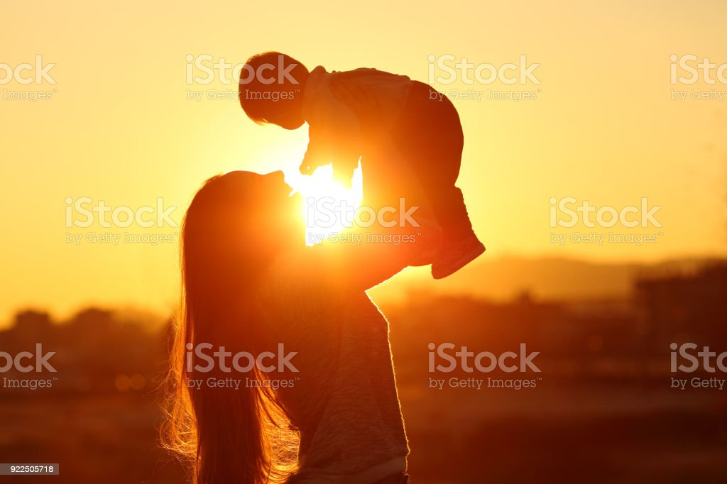 Mother raising her kid son at sunset with the sun in the middle stock photo