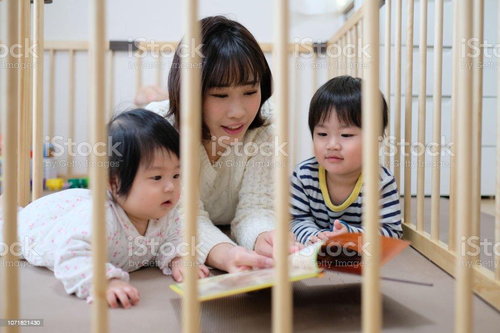 母親は、赤ちゃんと幼児に本を読んでください。 ストックフォト