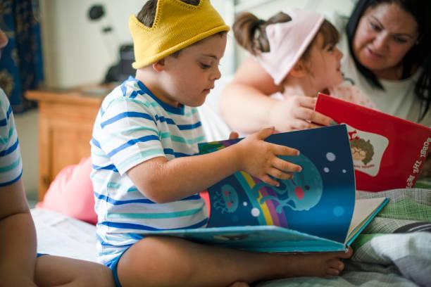 母の就寝時間の物語を読んで - disabilitycollection ストックフォトと画像