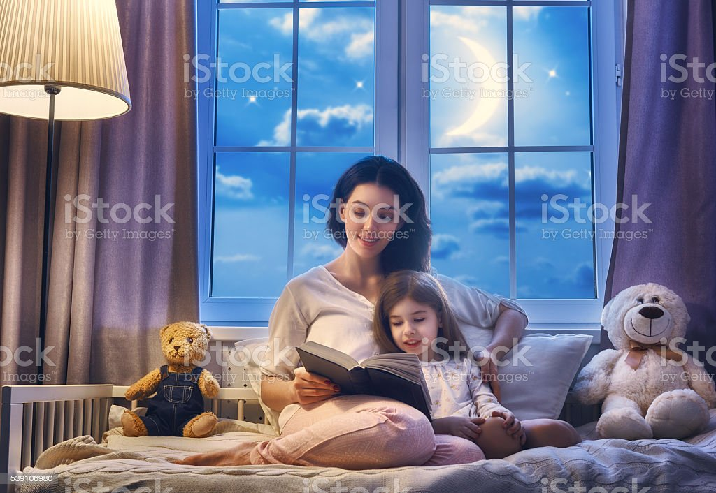 mother reading a book stock photo
