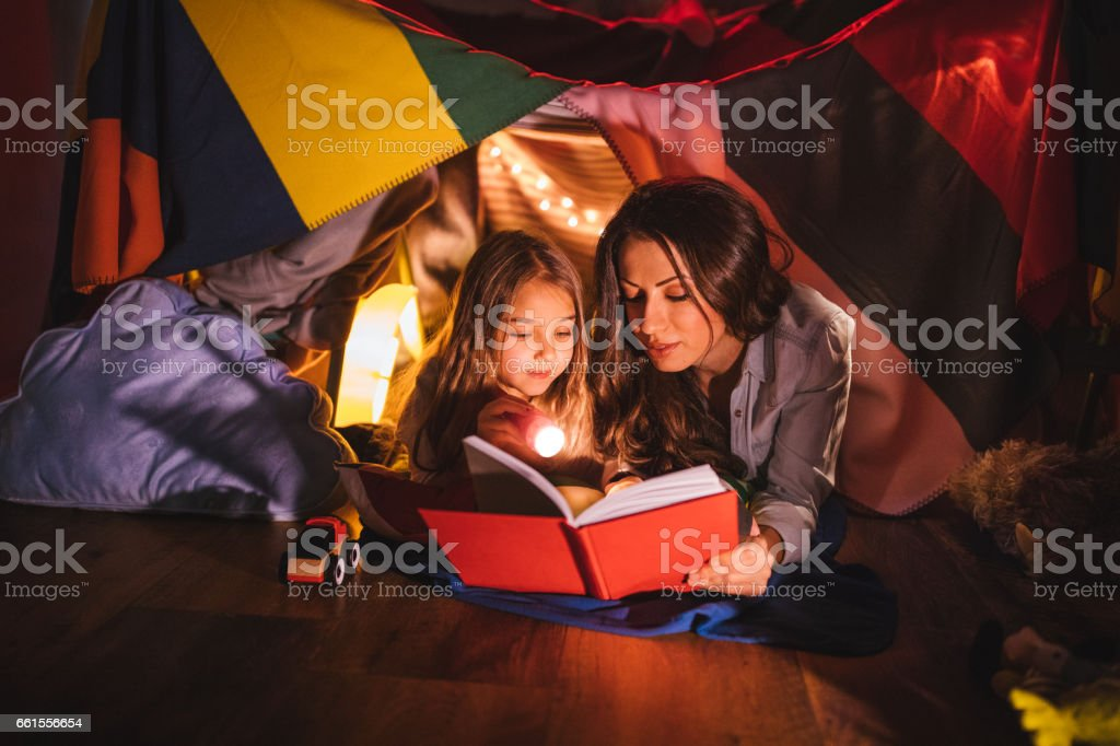Mother reading a book to her daughter at night stock photo