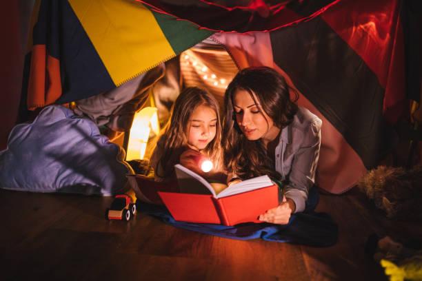mutter zu ihrer tochter in der nacht ein buch zu lesen - deckenleuchte kinderzimmer stock-fotos und bilder