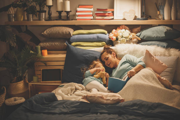 Mother reading a book to her daughter Mother is reading a book before bedtime while her sleepy daughter is lying down next to her. bedtime stock pictures, royalty-free photos & images