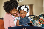 African American mother reading a book to her daughter