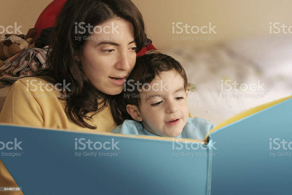 Mother reading a book to her son royalty-free stock photo