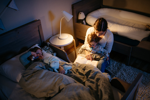 Young mother is reading a book to her two sons for a good night sleep. Night time with reading lamp. Horizontal photo.