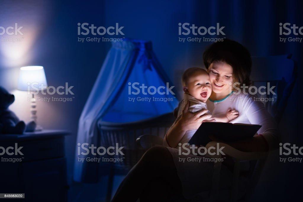 Mulher lendo um livro um pouco de bebê - foto de acervo