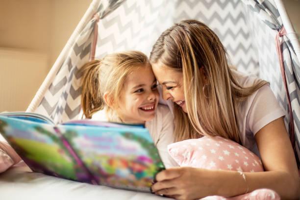 moeder het lezen van een verhaal aan haar dochter. - a little girl reading a book stockfoto's en -beelden