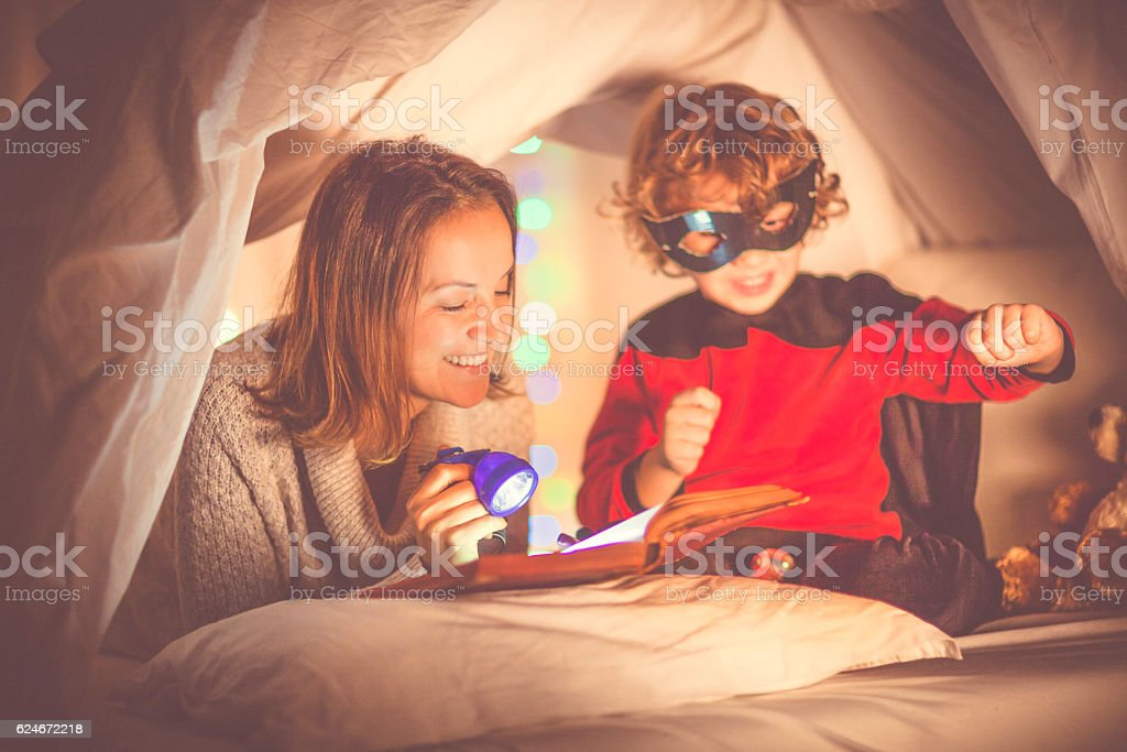 Mother reading a story to her son at bedtime - foto de stock
