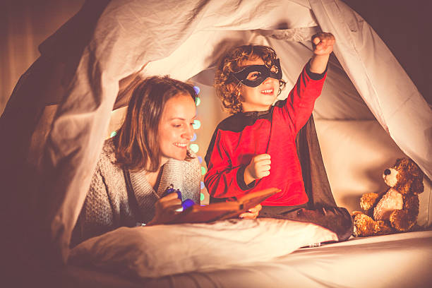 mother reading a story to her son at bedtime - kinder lesezelt stock-fotos und bilder