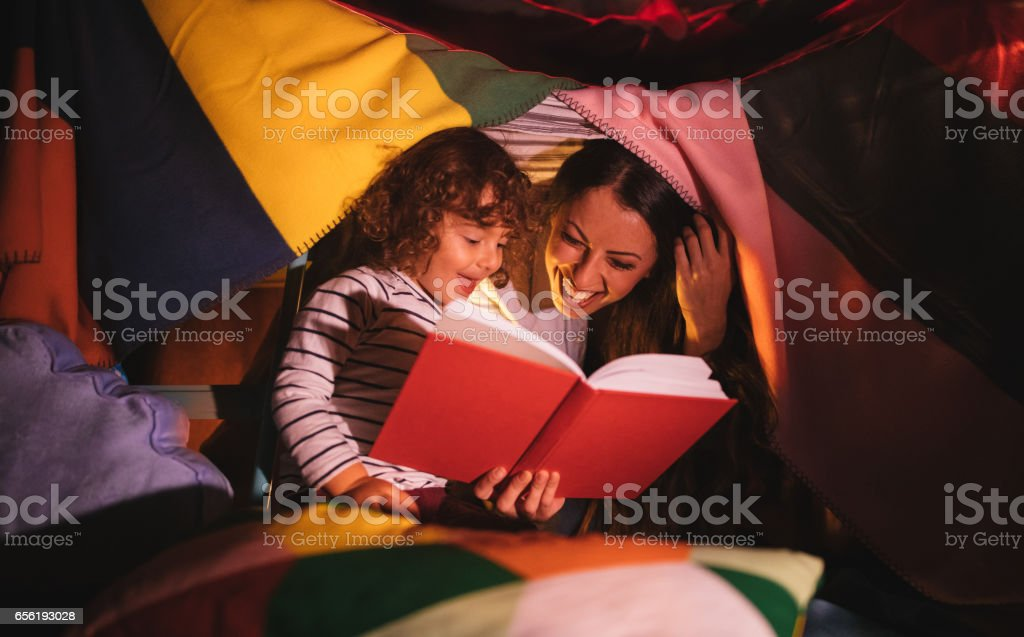 Mother reading a story to her son under bed covers stock photo