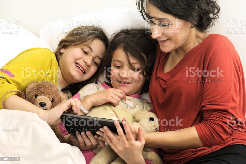 Mother reading bedtime e-story to daughters royalty-free stock photo