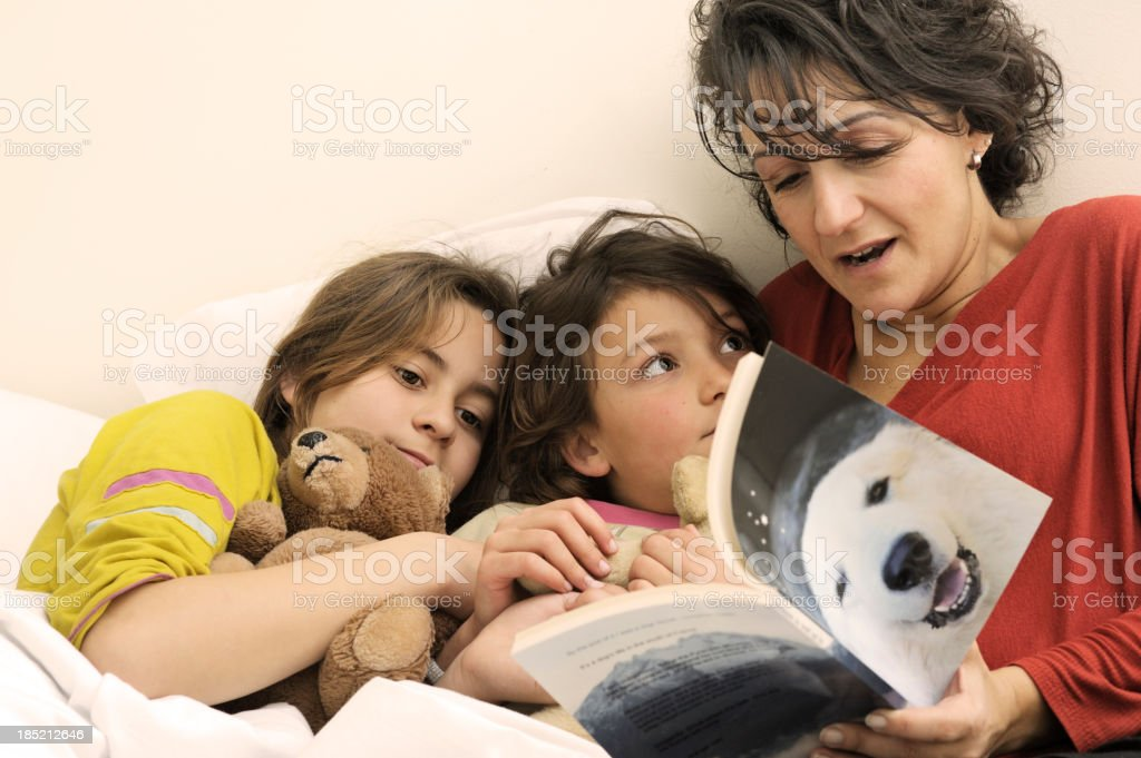Mother reading bedtime story to daughters stock photo