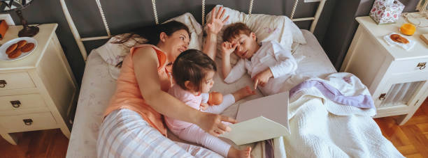 Mother reading book to her sons in the bed picture id1215315347?b=1&k=6&m=1215315347&s=612x612&w=0&h=jhnc4mmk8wtysijz68x4cai0cyhqczznshw n3t wuw=