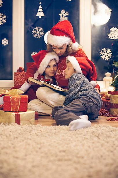 mutter liest christmas story, ihre kinder - nikolaus geschichte stock-fotos und bilder