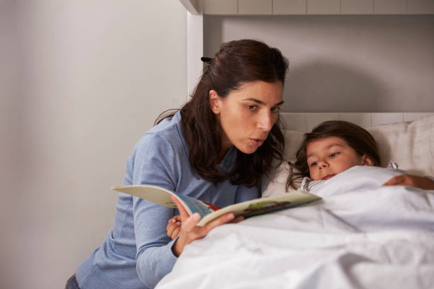 Mother Reading Story To Son At Bedtime stock photo