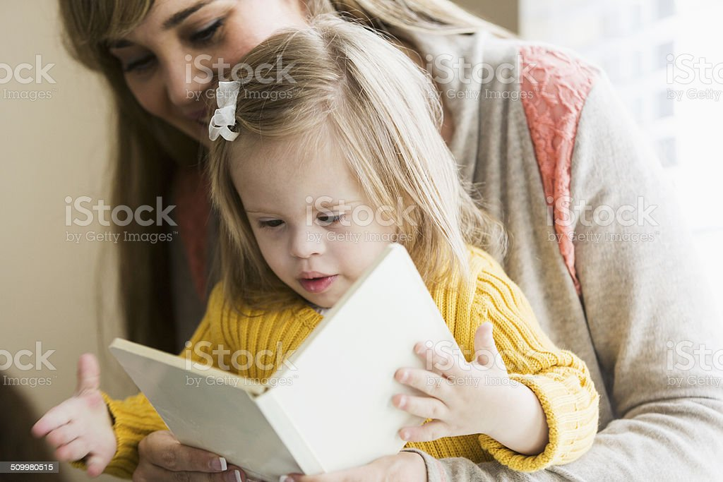 Mother reading to daughter with down syndrome stock photo
