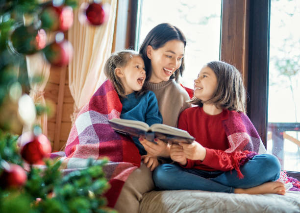 mother reading to daughters near Christmas tree. stock photo