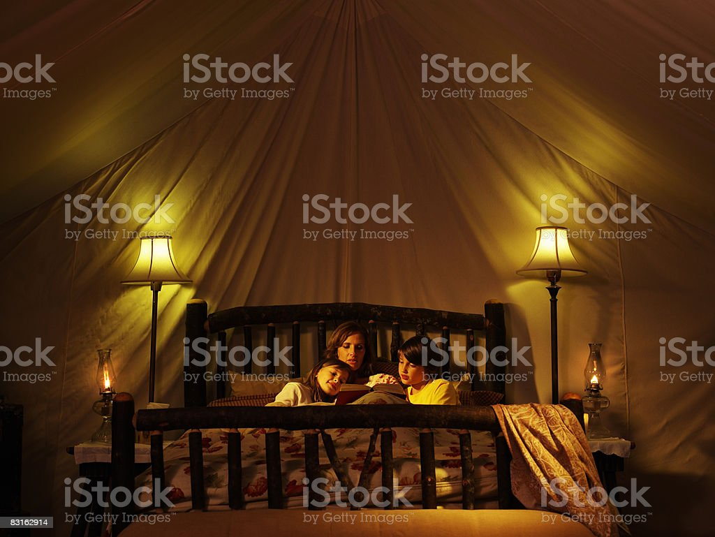 Mother reading to her children in bed inside tent. royalty-free stock photo