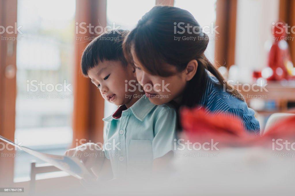 Mutter zu ihrem Sohn zu Hause lesen – Foto