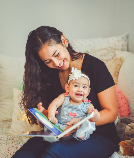 Mother reads book to sweet 6 month old baby stock photo