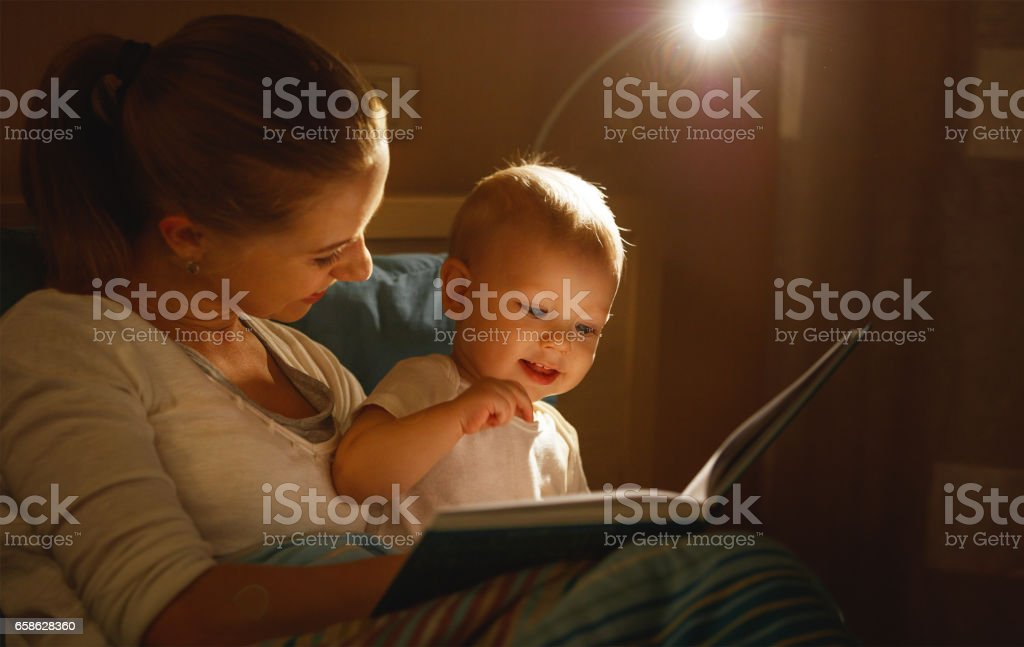 mother reads to baby book in bed stock photo