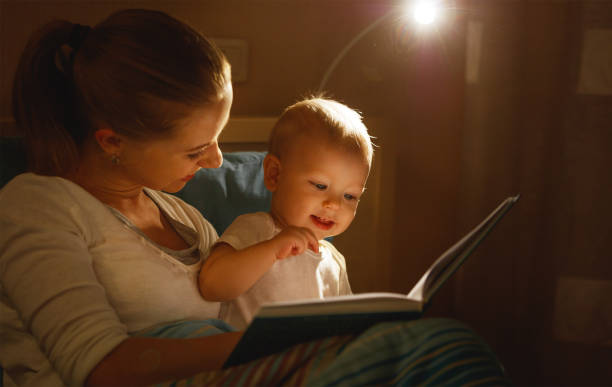 mother reads to baby book in bed - fairy tale stock pictures, royalty-free photos & images