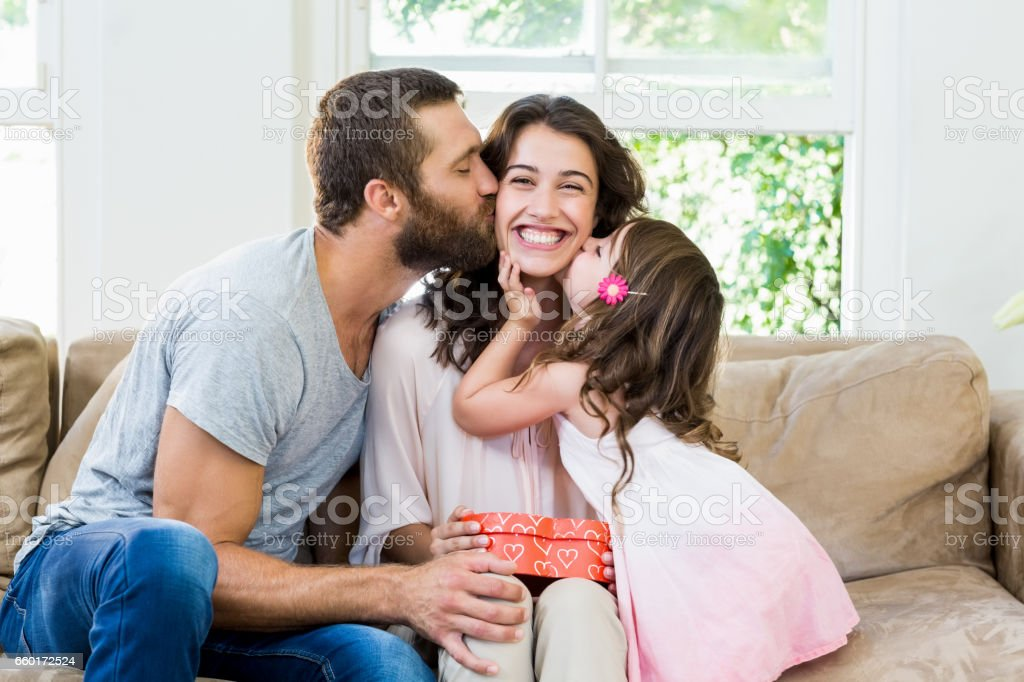 Mother receiving a gift from her husband and daughter stock photo